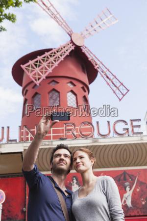 franciaparispareja fotografiando themself con smartphone frente