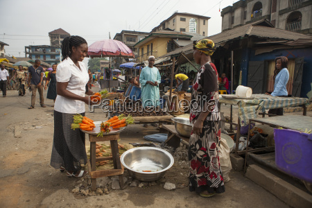 a woman buying carrots in the