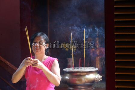 buddhist worshipper with incense sticks khanh
