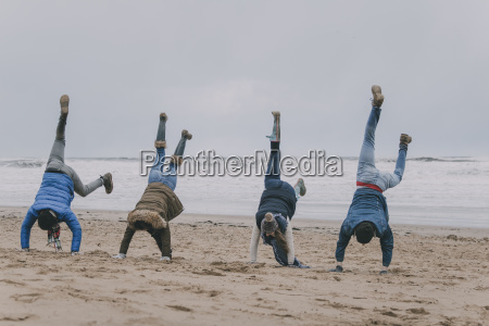 friends, doing, handstands, on, a, winter - 23019325